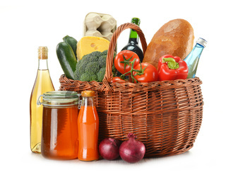 Grocery in wicker basket isolated on white