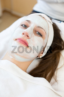Cosmetician giving client facial skincare mask