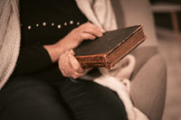Elderly Caucasian Woman Holds An Antique Book In Her Hands