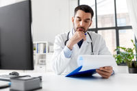 stressed male doctor with clipboard at hospital