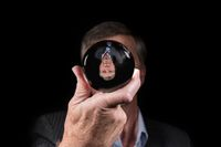 Senior businessman reflected upside down in a glass crystal ball to show world upside down