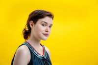 Close up fashion portrait beautiful young brunette woman on yellow background. Copy space.