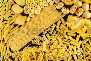 Pasta background texture, a flat lay of many different pasta types, shot from the top on black