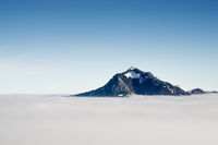 Mountain stick out of inversion fog cloud layer. Above the clouds concept for outstanding Business ideas, foresight and visonary leadership. Gruenten, Allgau Alps, Bavaria, Germany.