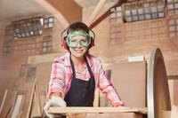 Frau als Schreiner beim Holz schleifen