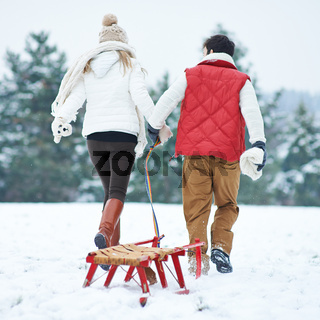 Paar im Winter zieht Schlitten