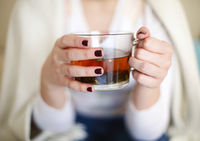 Woman drinking herbal tea at home