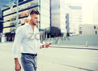 man with headphones and smartphone listening music