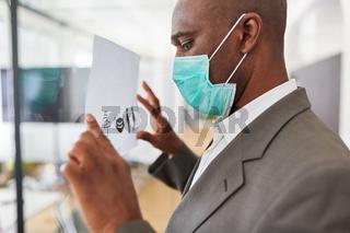 Geschäftsmann befestigt Aushang mit Hygieneregeln im Büro