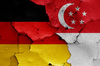 flags of Germany and Singapore painted on cracked wall