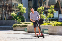 Young casual active sporty businessman in urban city center, wearing shirt and shorts, holding laptop bag, riding to work on electric scooter on a hot summer day