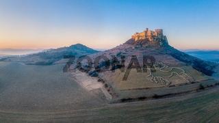 Spis Zipser Castle above valley at sunset or sunrise
