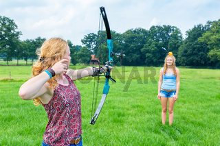 Girl aims arrow of compound bow at apple on woman
