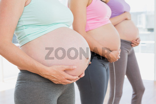 Pregnant women standing in a line holding their bumps