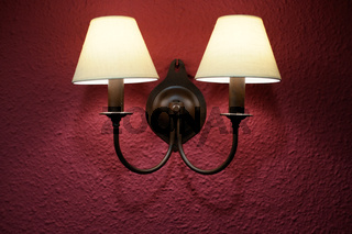 Two bulbs wall sconce over pink wall