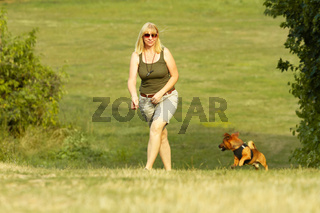 Woman hiking with her small dog in the summer landscape