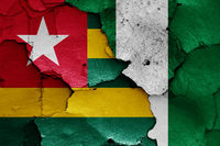 flags of Togo and Nigeria painted on cracked wall