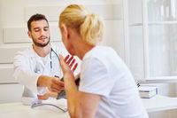 Arzt misst Blutdruck bei Patientin