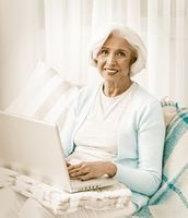 Happy Grandmother Using Computer Technologies In Laptop