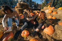 Young girls lie on haystacks among pumpkins.