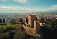 Aerial picturesque drone point of view Granada castle surrounding lands and cityscape, Alhambra or Red Castle, located on top of hill al-Sabika. Moorish palace fortress complex in Andalusia, Spain