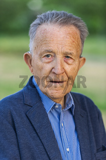 Portrait of an old man in a jacket looking seriously