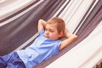 Preschoole boy lying in a hammock at summer day