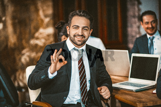 Intelligent Business Person shows Ok Sign Posing at Camera