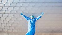 Mediziner mit ausgestreckten Händen vor Klinik in Schutzkleidung