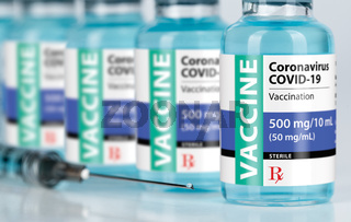 Coronavirus COVID-19 Vaccine Vials and Syringe On Reflective Surface