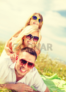 smiling family in sunglasses lying on blanket