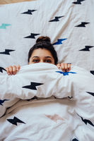 Closeup of Lovely young Woman Lies in Bed Covered with Blanket.