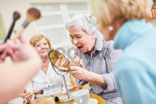 Seniorin als Best Ager beim Schminken mit dem Lippenstift im Senioren Schminkkurs