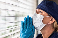 Prayerful Stressed Female Doctor or Nurse On Break At Window Wearing Medical Face Mask