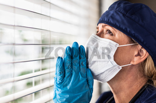 Prayerful Stressed Female Doctor or Nurse On Break At Window Wearing Medical Face Mask