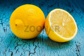 Lemon and cut half slice on blue wooden background