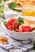 Porridge of tiny pancakes with berries. Trendy food.
