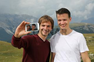 Freunde schießen ein Foto mit dem Smartphone im Urlaub