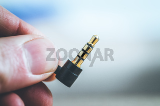 Audio jack concept: Close up of male fingers holding a 3.5mm audio jack