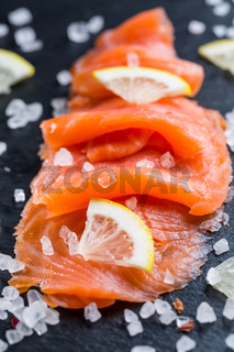 Smoked salmon with lemon and sea salt on black background. Healthy food concept.