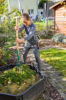 Child helping in the garden - adding lawn cuttings into composting bin