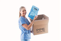 Nurse or doctor holding a Category 3 Coverall PPE for infection control
