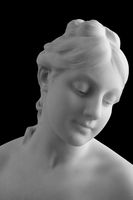 White marble sculpture head of young woman. Statue of sensual renaissance art era naked woman in circlet antique style isolated on black background