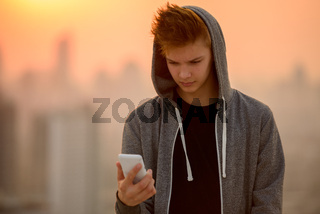 Young handsome teenage boy against view of the city outdoors
