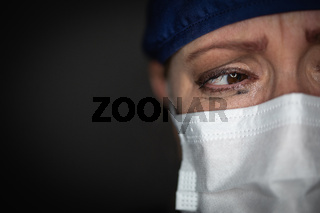 Tearful Stressed Female Doctor or Nurse Wearing Medical Face Mask on Dark Background