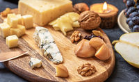 Cheese plate from different kind of cheese - Emmental, Homemade, Parmesan, blue cheese, bread sticks, walnuts, raisin, pear, grapes on a table
