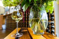 glass of white wine and flowers vase