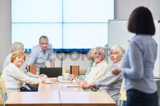 Dozentin mit einer Gruppe Senioren in einem VHS Kurs für Weiterbildung im Alter