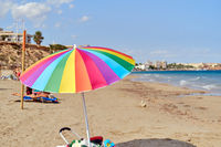 Multi colored parasol on the beach of Mil Palmeras, Spain
