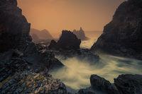 Sea fog and sunrise on sharp craggy coastline